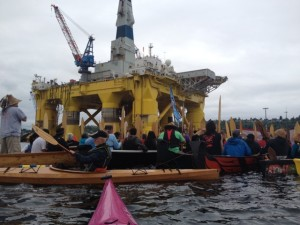 Native canoes and kayakers gathered beside the Shell drilling rig