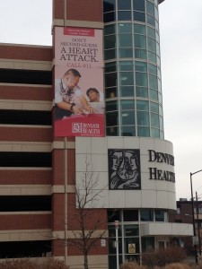 Banner on side of Denver Health of Brian helping a patient